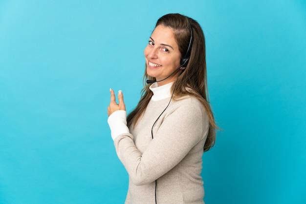 Молодая женщина-телемаркетер над изолированной синей стеной, указывая назад