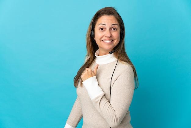 자랑스럽고 자기 만족 고립 된 파란색 벽 위에 젊은 텔레마케터 여자