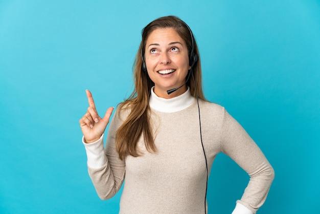 Молодая женщина-телемаркетер над изолированной синей стеной думает об идее, указывая пальцем вверх