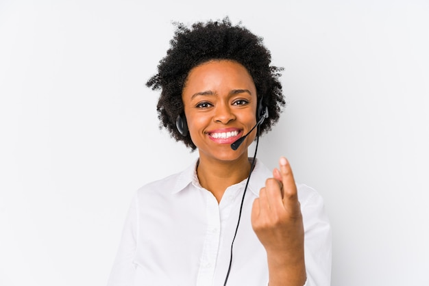 Young telemarketer woman pointing with finger at you as if inviting come closer
