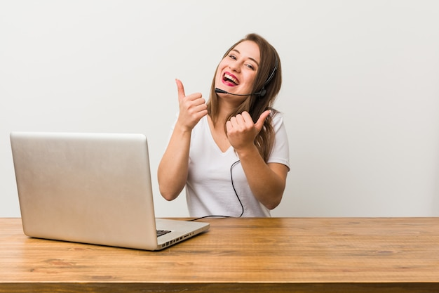 Young telemarketer woman raising both thumbs up, smiling and confident.