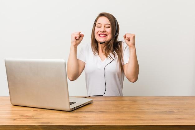 拳を上げて、幸せと成功を感じている若いテレマーケティングの女性。利佳國際電子。