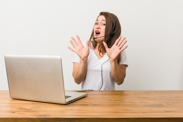 Young telemarketer woman rejecting someone showing a gesture of disgust.