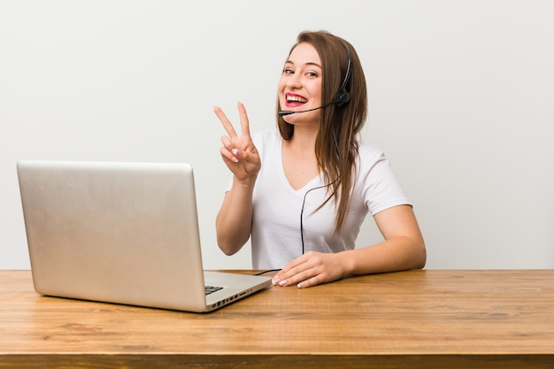 Young telemarketer woman showing victory sign and smiling broadly.