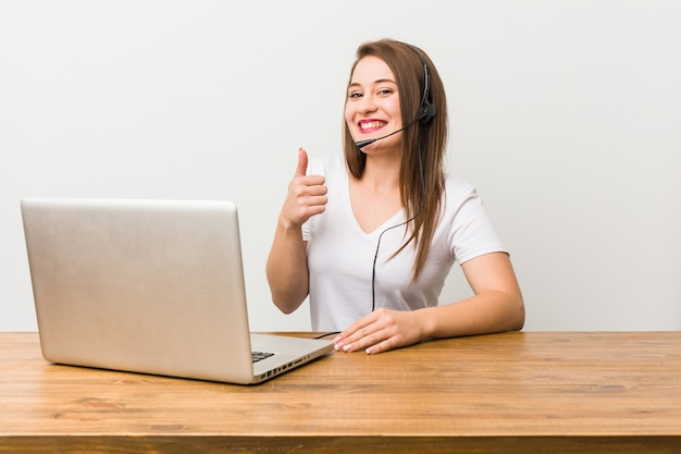 Young telemarketer woman smiling and raising thumb up