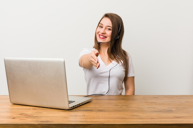 Young telemarketer woman stretching hand at camera in greeting gesture.