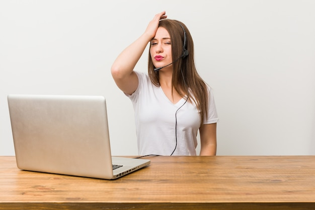 Young telemarketer woman tired and very sleepy keeping hand on head