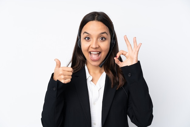 Young telemarketer woman on white showing ok sign and thumb up gesture