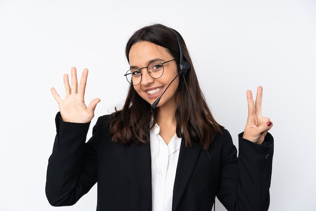 Young telemarketer woman on white wall counting seven with fingers