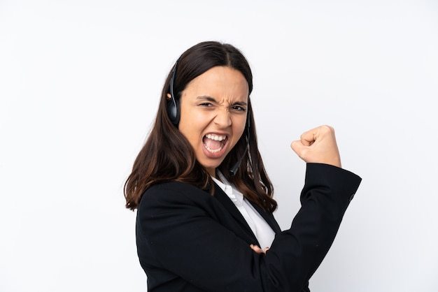 Young telemarketer woman on white wall doing strong gesture