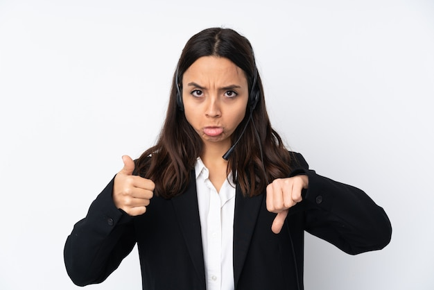 Young telemarketer woman on white wall making good-bad sign