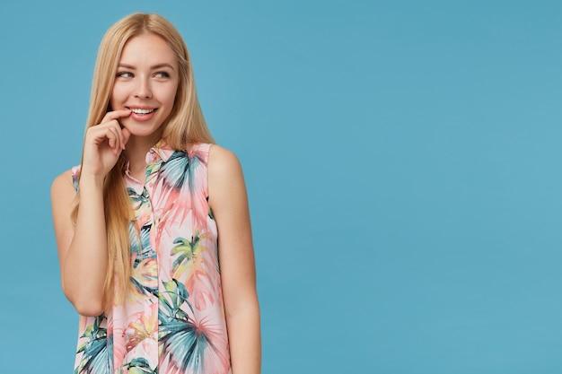 고립 된 매력적인 미소로 옆으로 보는 동안 캐주얼 헤어 스타일을 가진 젊은 부드러운 금발 아가씨는 언더 립에 앞발을 유지