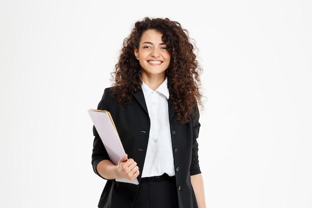 Молодая нежная кудрявая девушка держит документы