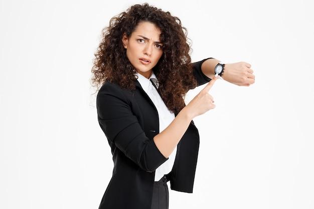 Giovane ragazza riccia tenera che guarda l'orologio e preoccupato che il ritardo