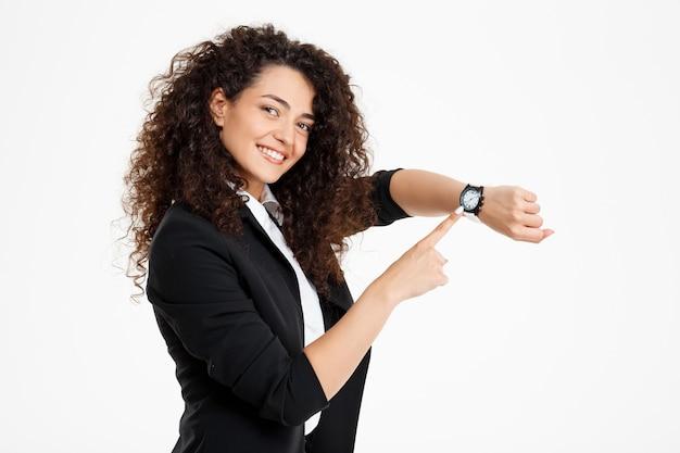 Giovane ragazza riccia tenera che mostra il suo orologio