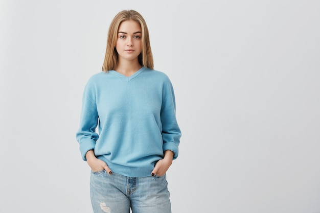Young tender fair haired teenage girl with healthy skin wearing blue top looking  with serious or pensive expression. caucasian woman model with hands in pockets posing indoors