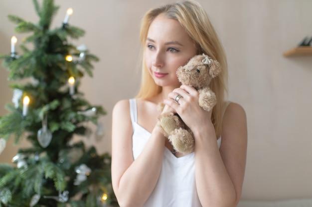 ネグリジェの柔らかい少女はクリスマスツリーとおもちゃのクマを抱擁します。