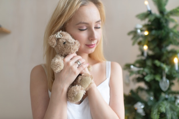 Young tender girl in nightie hugs toy bear with christmas tree on background.