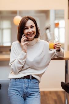 若い柔らかい女性が電話で話しているキッチンにいます。