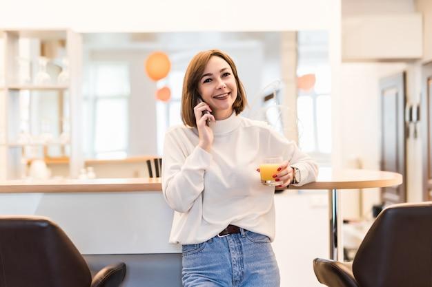 若い優しい女性が電話で話しているとオレンジジュースのガラスを保持しています。