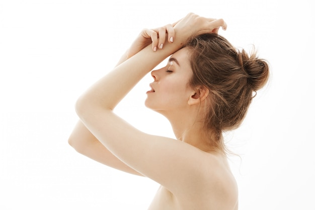 Young tender nude woman with bun posing over white background. closed eyes. profile.