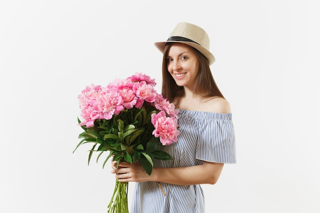 Young tender woman in blue dress, hat holding bouquet of beautiful pink peonies flowers isolated on white background. st. valentine's day, international women's day holiday concept. advertising area.