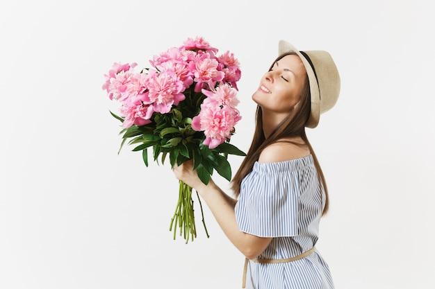 파란 드레스를 입은 젊은 부드러운 여성, 모자를 들고, 흰색 배경에 격리된 분홍색 모란 꽃의 꽃다발을 킁킁거리고 있습니다. 성 발렌타인 데이, 국제 여성의 날 휴일 개념. 광고 영역입니다.