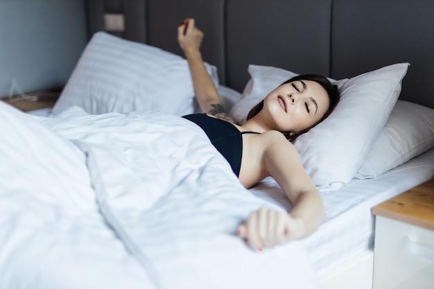 침대에 누워 그녀의 팔을 스트레칭 젊은 부드러운 여자