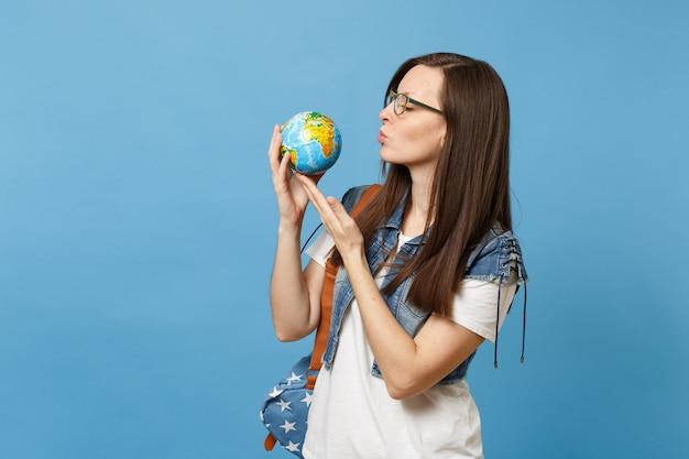 배낭을 메고 안경을 쓴 젊고 부드러운 여자 학생은 파란색 배경에 격리된 손에 지구로 공기 키스를 보냅니다. 고등학교에서 교육입니다. 행성을 저장합니다. 생태 환경 보호 개념입니다.