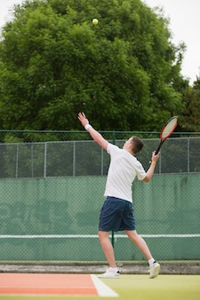 Young tennis player about to serve