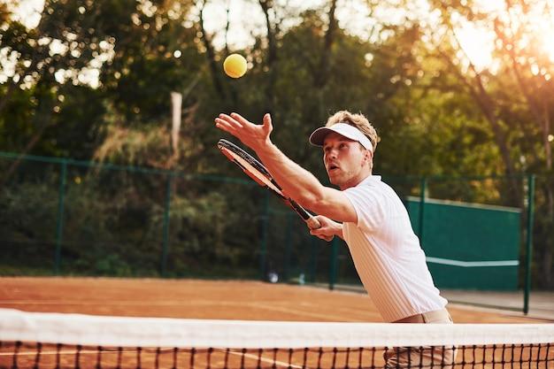 スポーツ服を着た若いテニス選手が屋外のコートにいます。