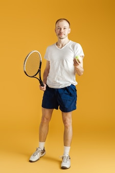 Young tennis player plays tennis on a yellow