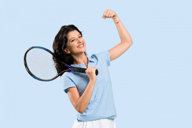 Young tennis player woman celebrating a victory