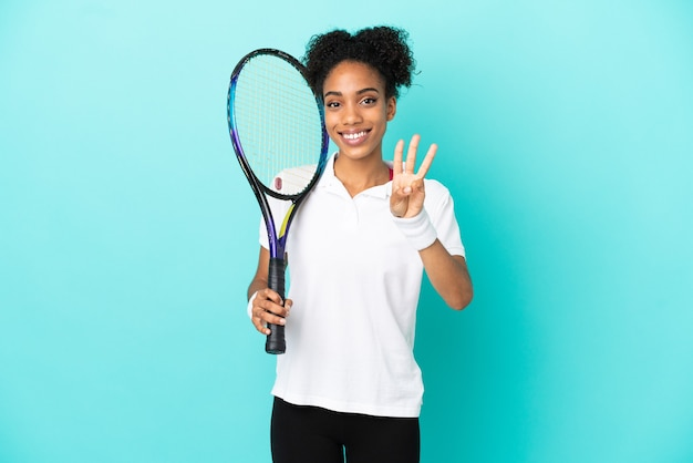 Young tennis player woman isolated on blue background happy and counting three with fingers