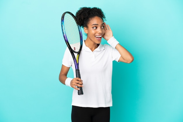 Young tennis player woman isolated on blue background listening to something by putting hand on the ear