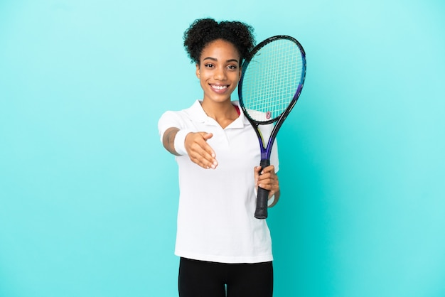 Young tennis player woman isolated on blue background shaking hands for closing a good deal
