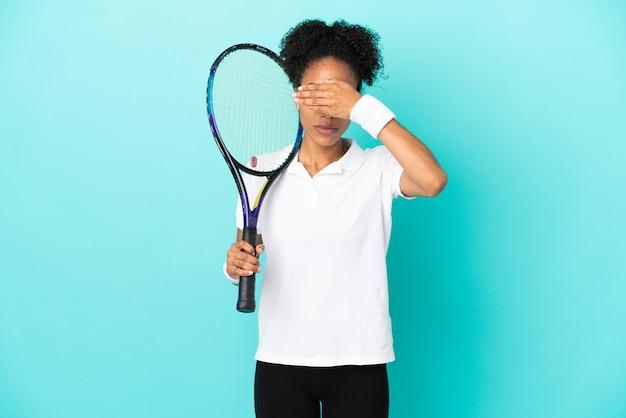 Женщина молодой теннисист, изолированные на синем фоне, закрывая глаза руками. не хочу что-то видеть