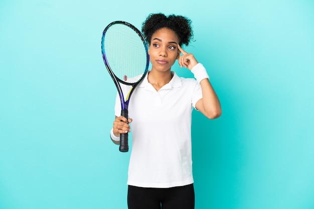 Молодая женщина-теннисистка изолирована на синем фоне с сомнениями и мышлением