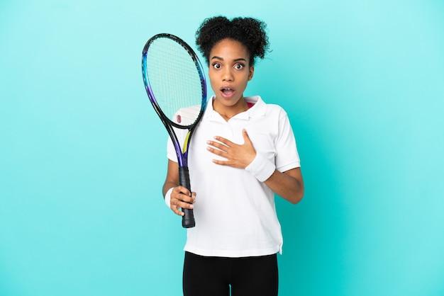 青い背景に孤立した若いテニスプレーヤーの女性は、右を見ながら驚いてショックを受けました
