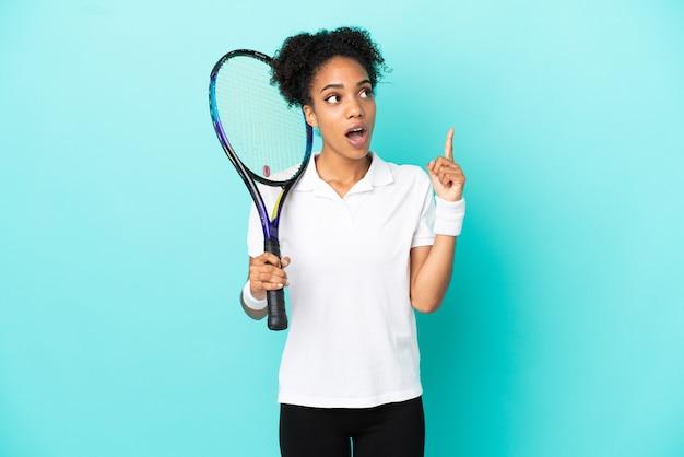 指を上に向けるアイデアを考えて青い背景に分離された若いテニスプレーヤーの女性