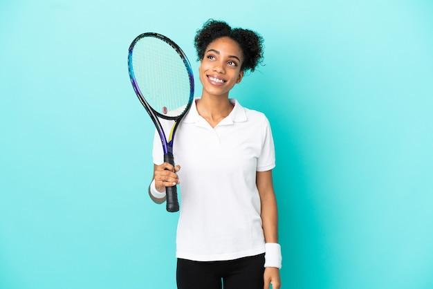 Молодая женщина-теннисистка изолирована на синем фоне, думая об идее, глядя вверх