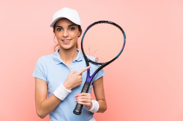 Young tennis player woman over isolated pink wall pointing to the side to present a product