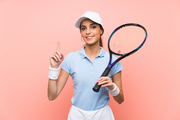 Young tennis player woman isolated pink wall pointing up a great idea