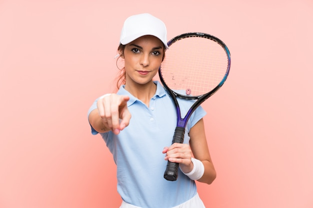 Young tennis player woman over isolated pink wall points finger at you with a confident expression
