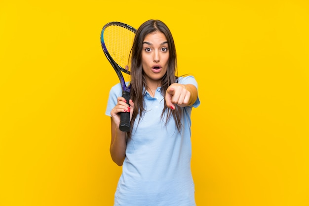 Young tennis player woman over isolated yellow wall surprised and pointing front