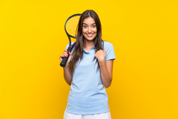 Young tennis player woman over isolated yellow wall with surprise facial expression