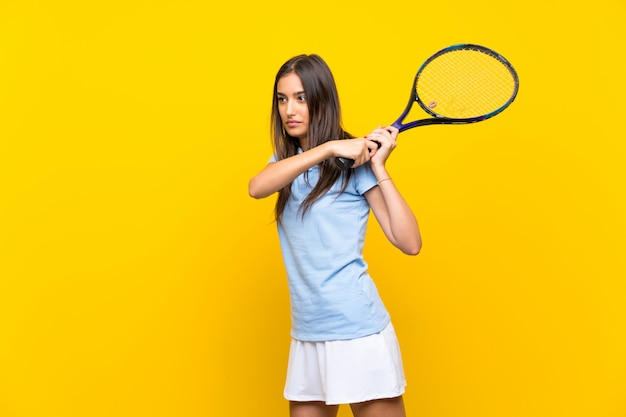 Young tennis player woman  isolated on yellow wall