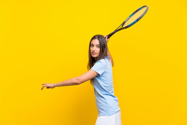 Young tennis player woman over isolated yellow wall