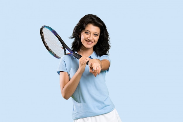 Young tennis player woman points finger at you with a confident expression