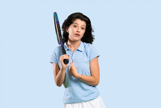 Young tennis player woman with surprise facial expression